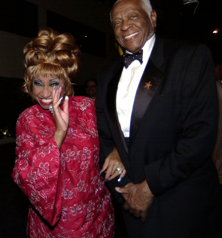 . Latin singer Celia Cruz, left, poses for members of the media with her husband, Pedro Cruz, while arriving at a party following the Latin Grammys hosted by Gloria Estefan in Los Angeles, Wednesday, Sept 18, 2002.  (AP Photo/E.J. Flynn)