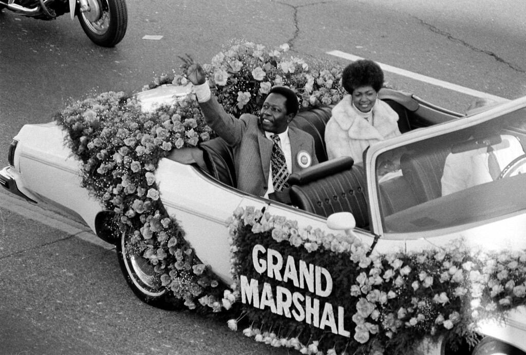 . Baseball player Hank Aaron waves to the crowd as grand marshal of the 1975 Tournament of Roses parade in Pasadena, Ca., Jan. 1, 1975.  Riding with him in the open car is his wife, Billye.  (AP Photo)