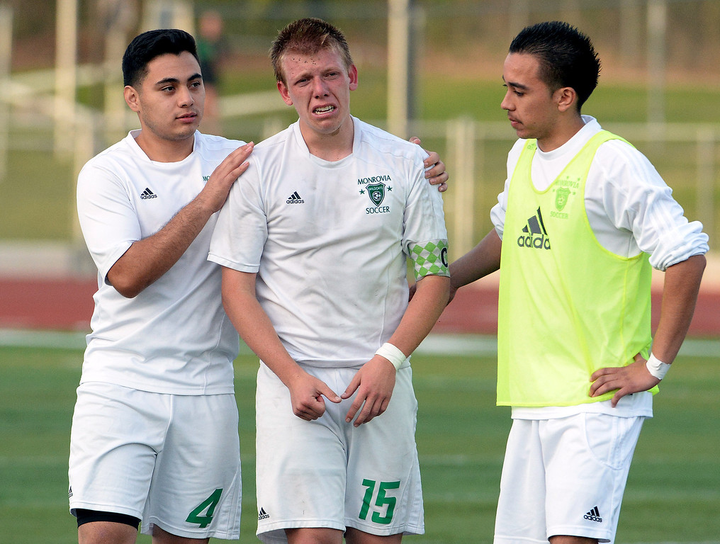 . Monrovia\'s Conor Sams (C) (15) is consoled by teammates after losing to Diamond Bar during a second round soccer match at Monrovia High School in Monrovia, Calif., on Tuesday, Feb.25, 2014. Diamond Bar won 3-2 on penalty kicks. (Keith Birmingham Pasadena Star-News)