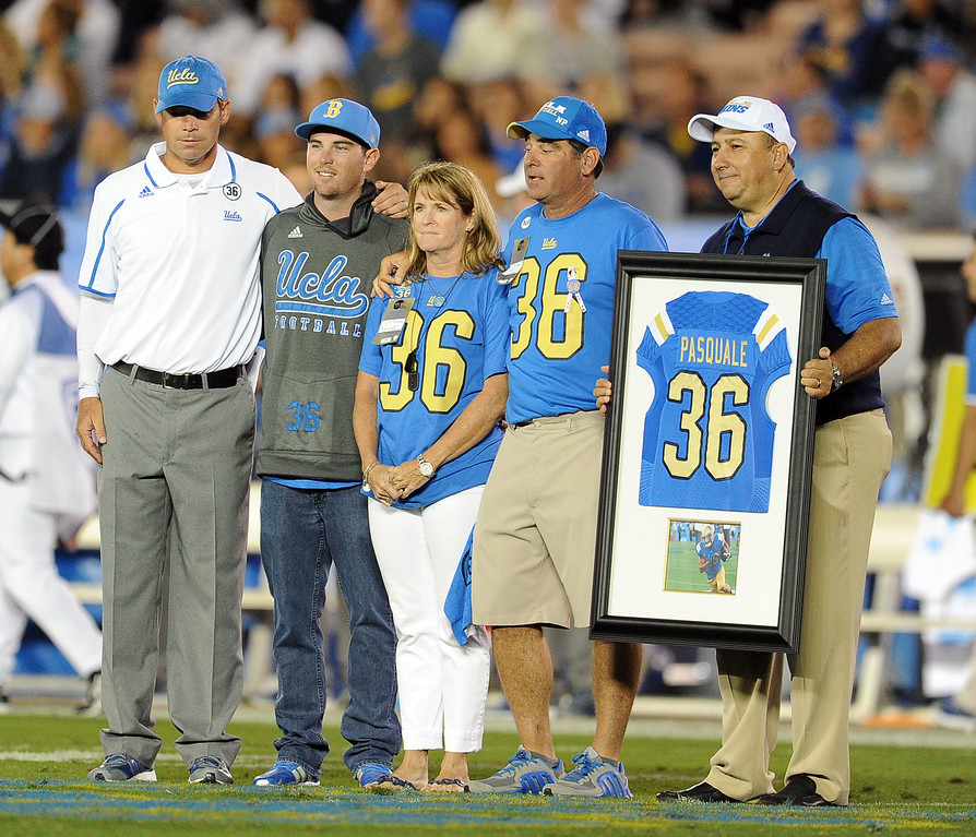 . UCLA head football coach Jim Mora, left, along with Athletic Director Dan Guerrero, right, presented the family of Nick Pasquale, the UCLA receiver who was struck and killed by a car on Sept. 8th with a jersey between the 1st and 2nd quarter their college football game against New Mexico State in the Rose Bowl in Pasadena, Calif., on Saturday, Sept. 21, 2013. Nicks brother Aj, second from left with his parents Laurie and Mel Pasquale.   (Keith Birmingham Pasadena Star-News)