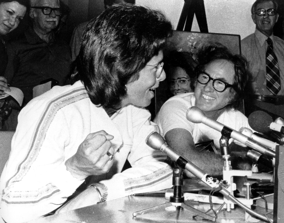 . Tennis player Billie Jean King, left, makes a fist while she answers a question at a news conference in Houston, Tex., on Wednesday, Sept. 20, 1973.  At right is Bobby Riggs smiling as King makes her answer.  (AP Photo)
