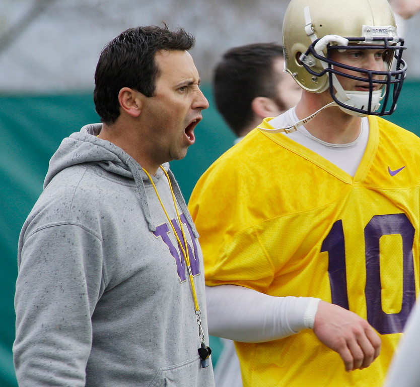 . Steve Sarkisian, Washington\'s new head coach, left, yells instructions to players as he stands with quarterback Jake Locker, during practice drills, Tuesday, March 31, 2009, at Husky Stadium in Seattle. Tuesday was the first day of spring NCAA college football practice for Washington. (AP Photo/Ted S. Warren)