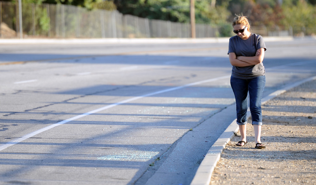 . A family member of the children who were killed walks along accident site during a vigil for those who died in a car crash including  two children and a man along the 3500 block of San Gabriel River Road on Friday, June 14, 2013 in Industry, Calif.  (Keith Birmingham/Pasadena Star-News)