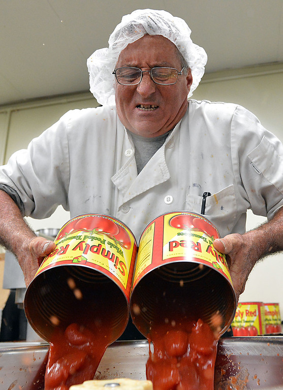 . Gary Hummel pours tomatoes into a mixer during the preparation of Saverion\'s Marinara Sauce at Da\'Kine Foods in Newport Beach. Following the successful launch of Saverino\'s Italian Deli and Market in Redlands nearly two years ago, David Saverino is bottling the flavor of his business with the introduction of four separate sauces. In addition to selling the sauces at his deli, Saverino hopes to see his product on the shelves of local markets. (Photo by Rick Sforza/Redlands Daily Facts)