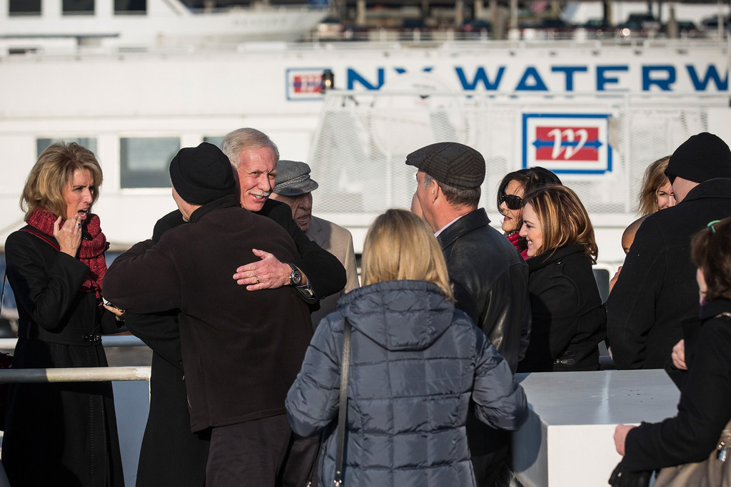 """. NEW YORK, NY - JANUARY 15:  Chesley \""""Sully\"""" Sullenberger (C), a retired airline captain famous for landing a commercial jet on the Hudson River,hugs a passenger from the flight on a New York Waterway ferry during a celebration for the five year anniversary of \""""The Miracle on the Hudson\"""" at a press conference and photo opportunity on January 15, 2014 in New York City. On January 15, 2009, Sullenberger took off from La Guardia airport while piloting US Airways Flight 1549 with 150 passengers and five crew members. The plane hit a goose shortly after take off, forcing Sullenberger to land the plane in the Hudson River; no one was killed.  (Photo by Andrew Burton/Getty Images)"""