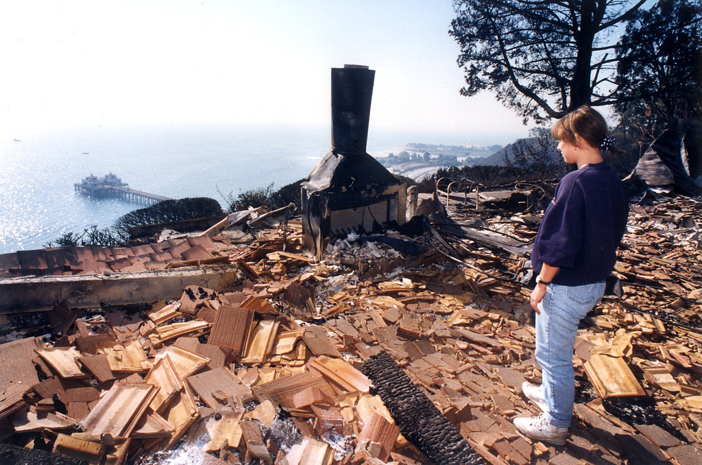 . Debby Annakin stands where the living room used to be at her parents\' house on Sweetwater Mesa Road overlooking the Malibu Pier.  (11/4/93)   Los Angeles Daily News file photo