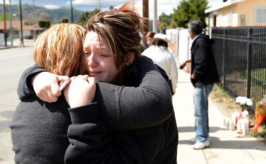 . Mitzi Burian, right, hugs her mother Yaneth Burian at a memorial where Kelly Jacinto-Burian was shot and killed in Pomona March 8. 2013. Jacinto-Burian was shot during a drive-by shooting a day earlier.  (Staff photo/Inland Valley Daily Bulletin)
