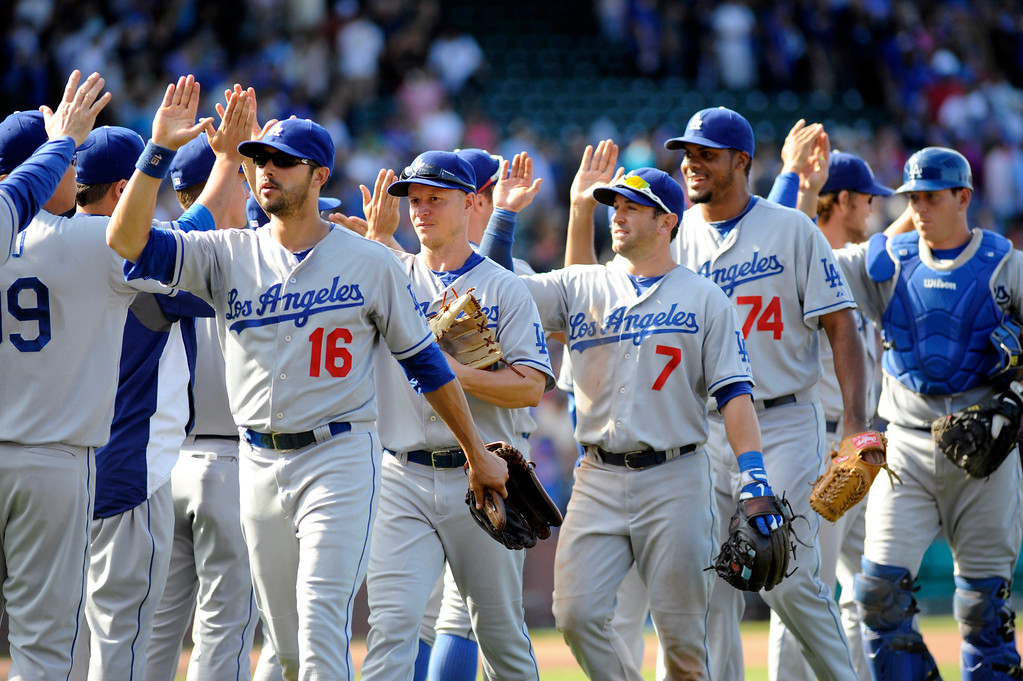 . Los Angeles Dodgers players high-five each other after their 1-0 victory over the Chicago Cubs in a baseball game, Sunday, Aug. 4, 2013, in Chicago. (AP Photo/Joe Raymond)