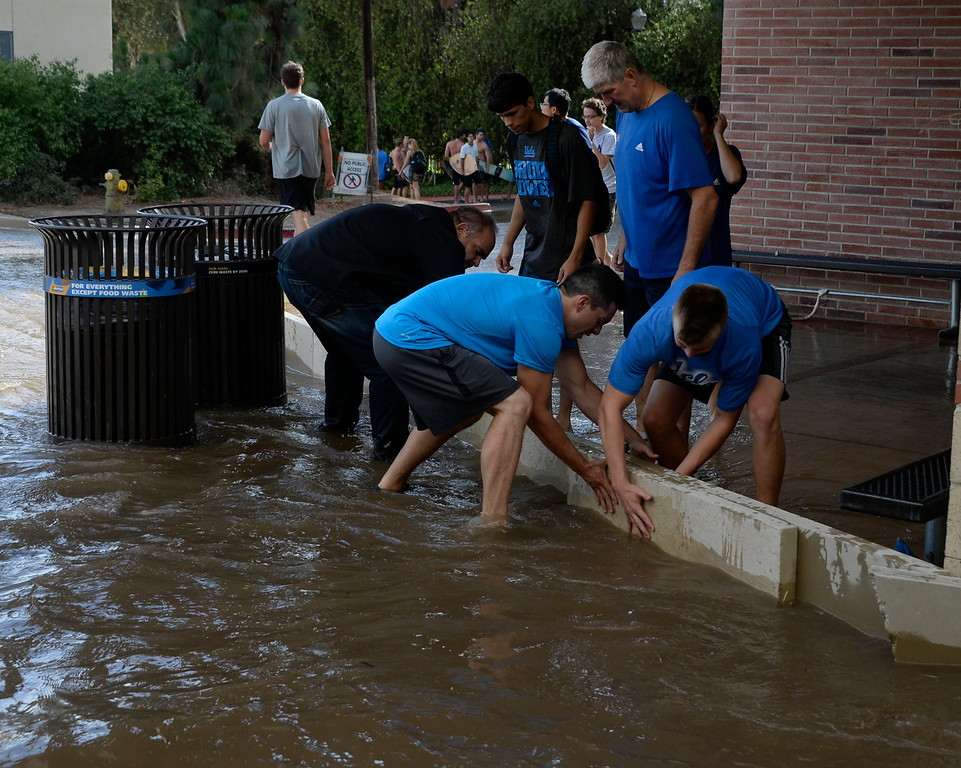 . July 29,2014. Westwood CA,  UCLA students make small dams to keep the water out  after a major water main break sent a geyser of water blasting through Sunset Boulevard north of the UCLA campus Tuesday, sending mud and water cascading down the street and inundating a number of vehicles as it made its way onto the campus. Photo by Gene Blevins/LA DailyNews