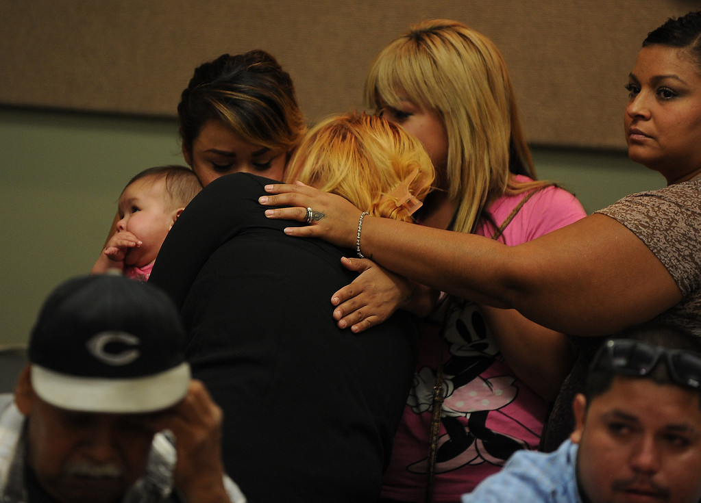 . Family members comfort each other during a press conference at the San Bernardino County Sheriff\'s Head quarters Thursday August 22, 2013 in San Bernardino. Daniel Olivera 26, of Hesperia was shot and killed at the AM/PM Arco convenience store on August 11, 2013 in Victorville.LaFonzo Carter/Staff Photographe