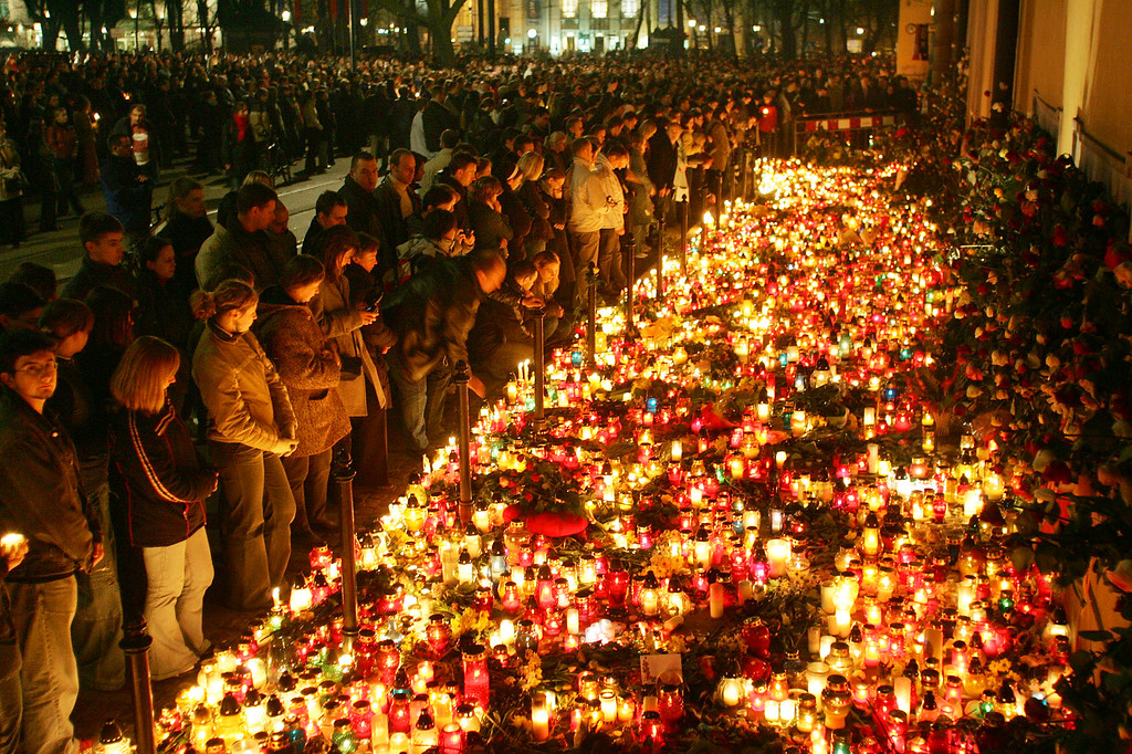 . People stand in front of a sea of burning candles at the bishop\'s residence in Krakow, southern Poland, Sunday April 3, 2005, the day after the death of Pope John Paul II was announced by the Vatican. Pope John Paul II  served here as priest and bishop. (AP Photo/Herbert Knosowski)