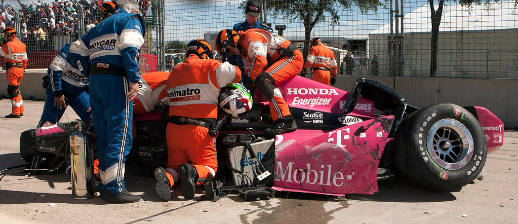 . Safety team members work to remove Dario Franchitti, of Scotland, from his car after a crash during the second IndyCar Grand Prix of Houston auto race, Sunday, Oct. 6, 2013, in Houston. (AP Photo/Juan DeLeon)