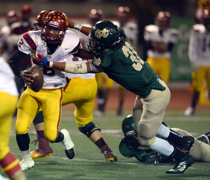 . Costa defender Jahlani Tavai (31) pressures Highland QB Donte Ross (2)  in first-half game action in the CIF Southern Section Northern Division first-round football game between the Highland High School Bulldogs and Mira Costal Mustangs at Costa Friday evening, 11/15/2013.  Photo for The Daily Breeze by Axel Koester, 11/15/2013.