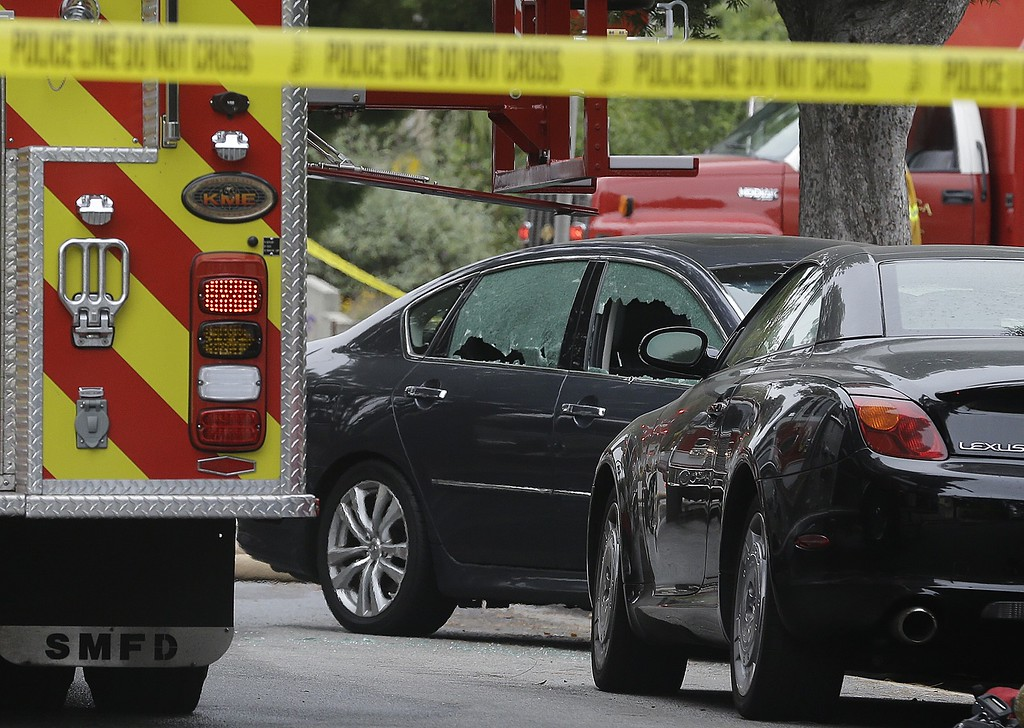 . A car with its windows broken stands near where shots were fired near Santa Monica College in Santa Monica, Calif., Friday, June 7, 2013.  Two people were found dead in a burned home near the college campus, where someone sprayed a street corner with gunfire, wounding at least three people, authorities said.(AP Photo/Reed Saxon)
