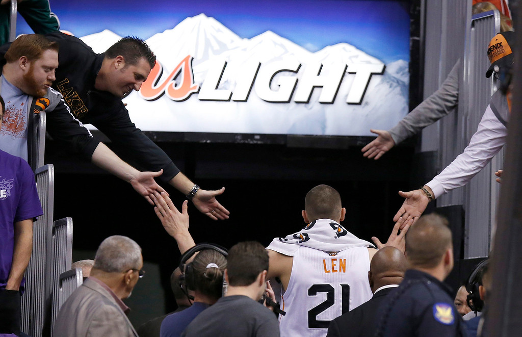 . Phoenix Suns\' Alex Len gets high-fives from Suns fans and Los Angeles Lakers fans after being ejected for his flagrant foul on Lakers\' Nick Young during the first half of an NBA basketball game Wednesday, Jan. 15, 2014, in Phoenix.  The Suns defeated the Lakers 121-114. (AP Photo/Ross D. Franklin)