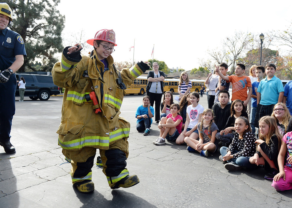. Valle Vista Elementary School fifth grader Hayden Pestel, 10, walks awkwardly in a fire suit after he was recognized as a hero Tuesday February 11, 2014 by the Rancho Cucamonga fire department at the school. Pestel awoke his sleeping grandfather Thursday night after the laundry room in his home caught fire allowing them both to escape the fire without injury. Damage to the home was set at $230,000. (Will Lester/Inland Valley Daily Bulletin)