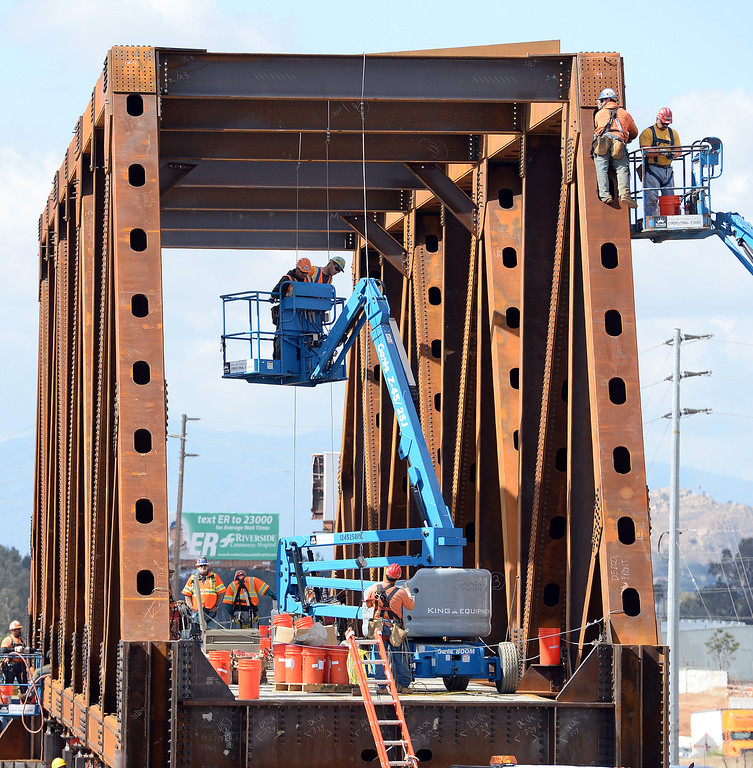 . Work continues on 4 train bridges off the 215 freeway in Grand Terrace Tuesday morning April 1, 2014. The bridges are 200 feet long, 23 feet wide and 30 feet tall and weigh 1.1 million pounds each. The bridges will be moved into a temporary position over the 215 freeway, to replace older bridges, this coming month which will result in a full freeway closure on a number of different days and nights between Iowa Avenue and Barton Road.  (Will Lester/Inland Valley Daily Bulletin)
