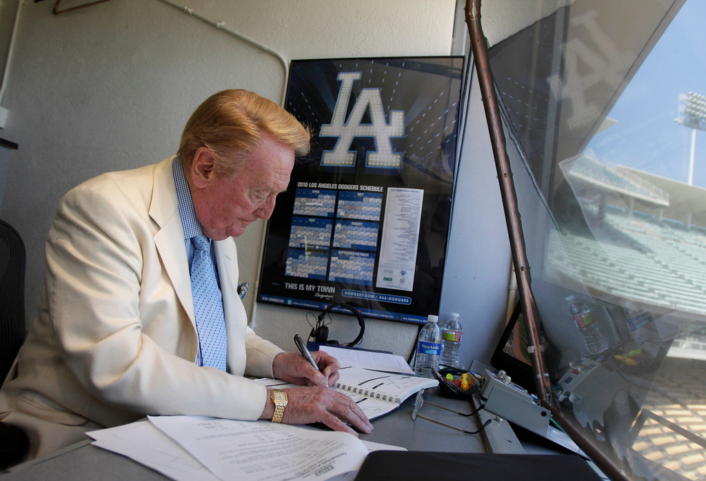 . Vin Scully works in his booth at Dodger Stadium in Los Angeles, Sunday, Aug. 22, 2010. cully will return to the broadcast booth to call Los Angeles Dodgers games next year for his 62nd season. The team said Sunday that the 82-year-old Hall-of-Famer will call all home games and road games against National League West opponents. (AP Photo/Jae C. Hong)