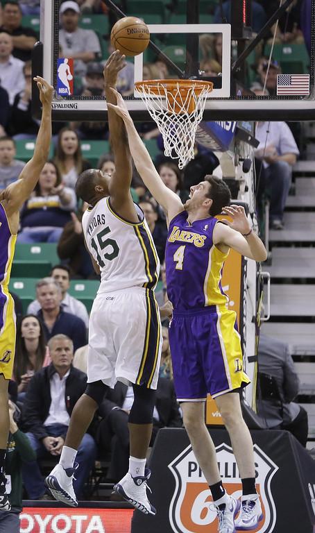 . Los Angeles Lakers Ryan Kelly (4) defends against Utah Jazz\'s Derrick Favors (15) in the first quarter during an NBA basketball game Monday, April 14, 2014, in Salt Lake City, Utah. (AP Photo/Rick Bowmer)
