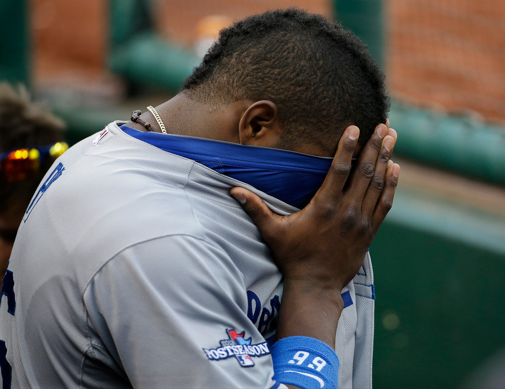 . Los Angeles Dodgers\' Yasiel Puig covers his eyes in the dugout during the seventh inning of Game 2 of the National League baseball championship series against the St. Louis Cardinals Saturday, Oct. 12, 2013, in St. Louis. (AP Photo/David J. Phillip)