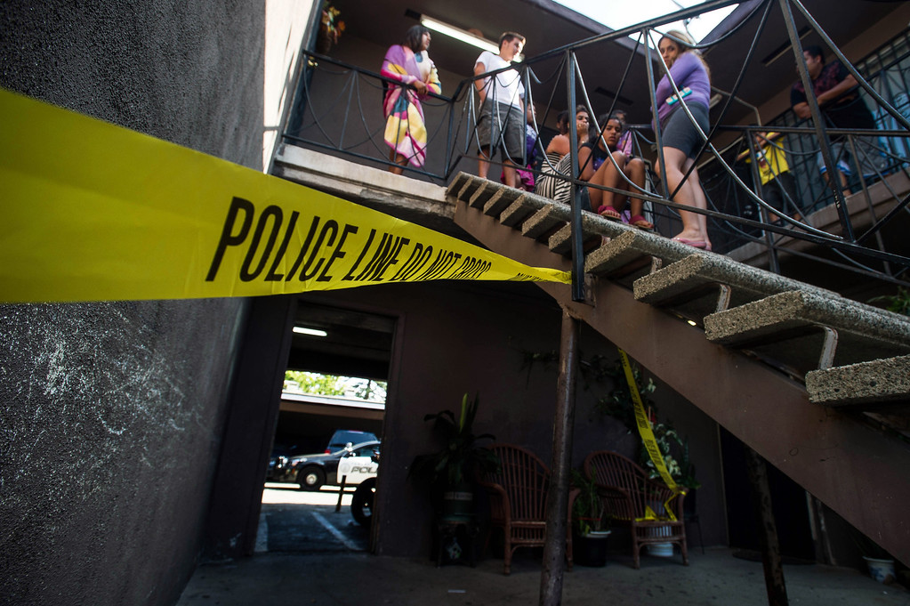 . Residents gathered outside their apartments as police investigate an early morning shooting death of a woman in the 700 block of San Francisco Avenue in Pomona on Monday, June 14, 2014. The woman\'s body was found in the carport area behind the complex. (Photo by Watchara Phomicinda/ San Gabriel Valley Tribune)