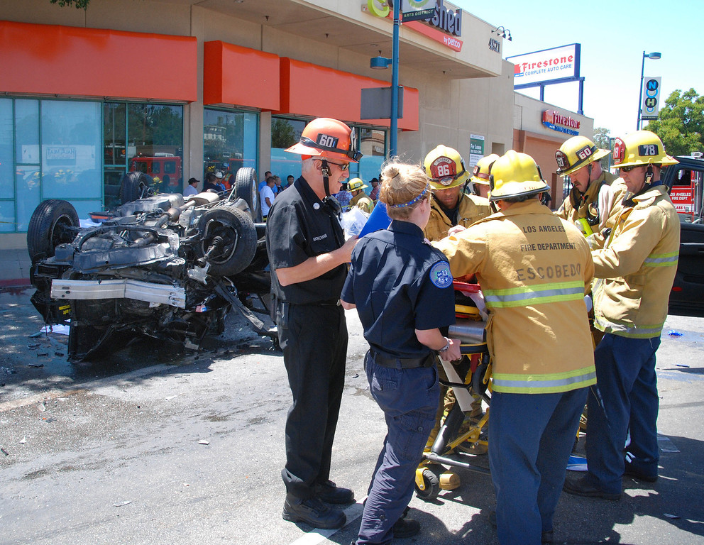 . North Hollywood, ca. LAFD firefighters work on one of four injured in a horrible three car accident at Lankershim Bl and Vinelans Av in North Hollywood this afternoon, A male in an overturned SUV was pronounced at the scene. The fore injured went to various hospitals with injures ranging from moderate to serious.