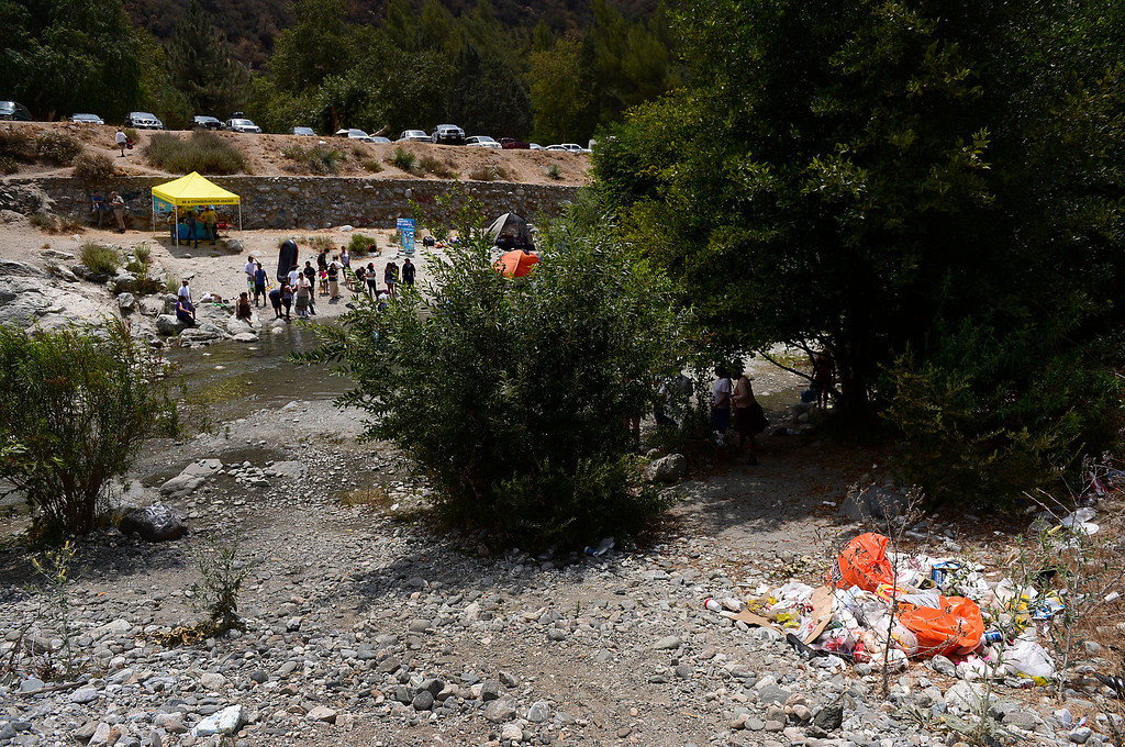 . The Urban Conservation Corps educates people and passes out orange bags for visitors to pack their garbage out along the East Fork of the San Gabriel River in the Angeles National Forest Saturday, July 20, 2013. Although the Urban Conservation Corps says their river trash count studies show less trash the area is still littered with garbage. (SGVN/Staff Photo by Sarah Reingewirtz)